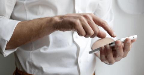 Geschäftsmann tippt auf ein Smartphone