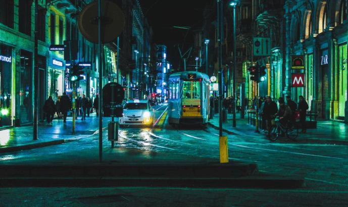 Strassenkreuzung mit Ampelanlagen, Strassenbahn und Auto bei Nacht