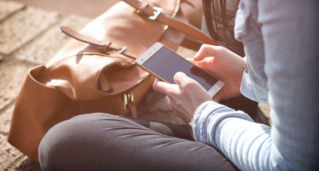 Eine Person sitzt am Boden und hält das Smartphone in den Händen.