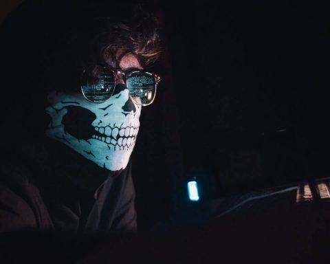 Ein Mann mit Totenkopfmaske und Sonnenbrille in einem abgedunkeltem Raum