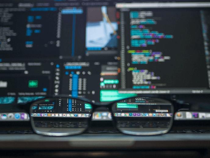 Eine Brille liegt vor einem abgedunkelten Bildschirm mit Programmiercode