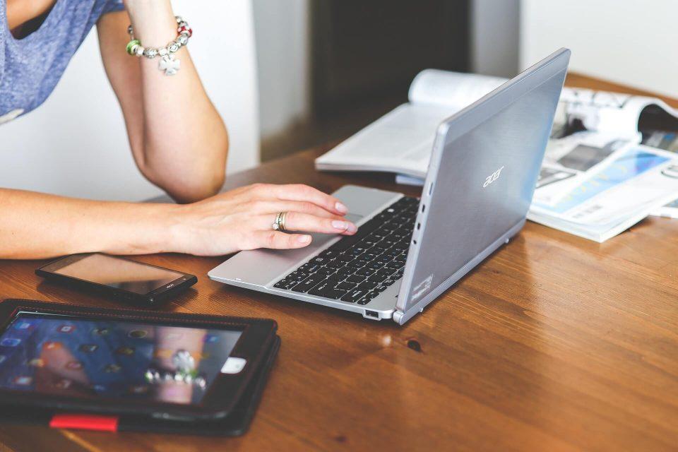 Frauenhände tippen am Notebook, daneben liegt ein Smartphone und ein Tablet