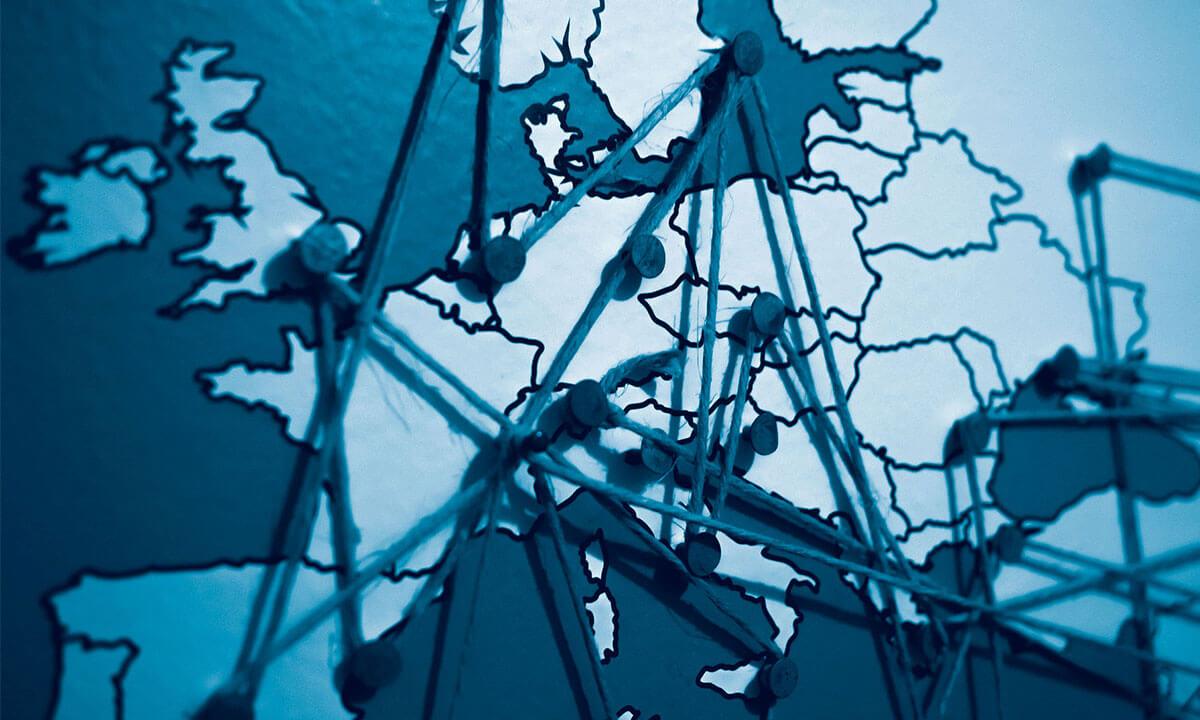 Auf einer Weltkarte an der Pinnwand sind verschiedene Routen mit Schnüren abgesteckt