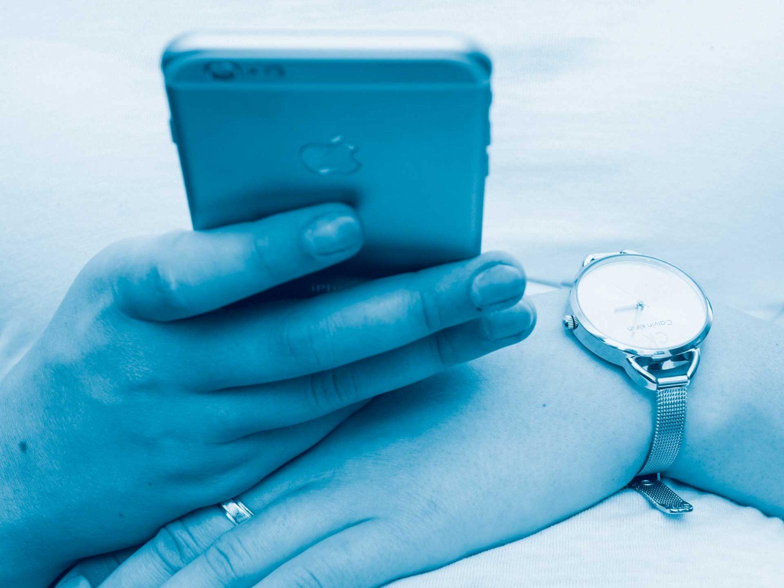 Hände mit einer Uhr am Handgelenk halten ein Smartphone