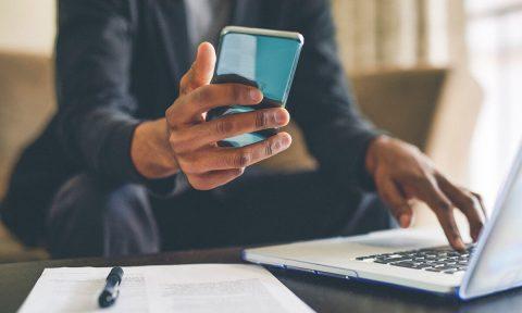 Mann hält Smartphone in der rechten Hand und berührt mit der linken Hand die Notebook-Tastatur